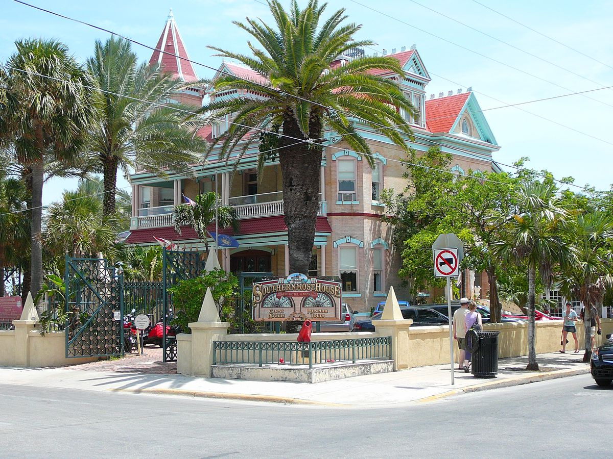 The exterior of the Southernmost House in Florida.  The facade is peach with blue decorative details. There are palm trees in front.