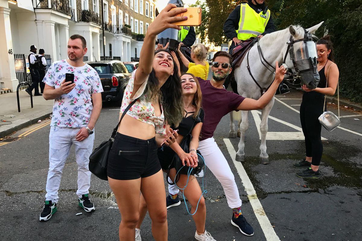 Two young women and a young man take a selfie in front of a horse pulling a carriage