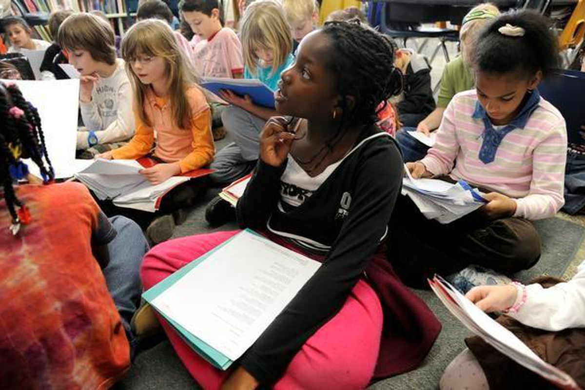 Anaelle Dahourou, 9, right, listens while her teacher, Anne Ertman, reads to the third- grade class at University Park Elementary School in Denver in 2010.