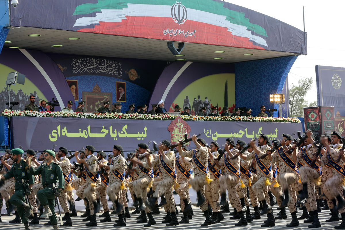 Soldiers raise their weapons in front of a shrine bearing the Iranian flag.