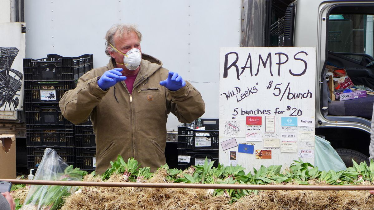 A man wearing a mask and gloves stands behind a table of neatly arranged green ramps.