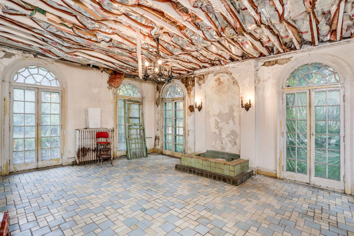 The sunroom has many white and blue floor tiles, a green-tiled fountain, and French doors leading outside. The ceiling is missing showing drywall and wood beams.