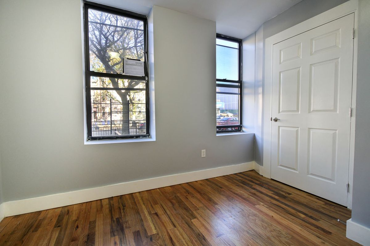A living area with hardwood floors, grey walls, and two windows.