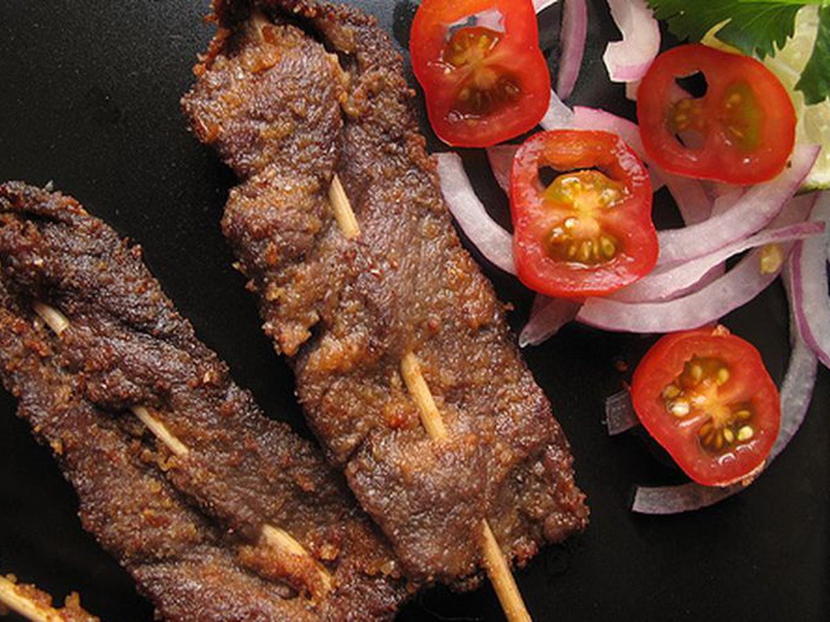 two skewers with thing slices of beef next to halves cherry tomatoes and sliced red onions