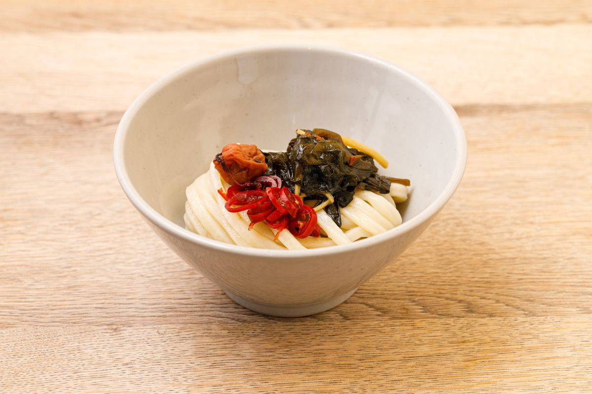 Acid fiends will find their kin in this triple-pickle udon, which features pickled wakame; pickled chilli; and umeboshi, served in a white bowl on a light wood table