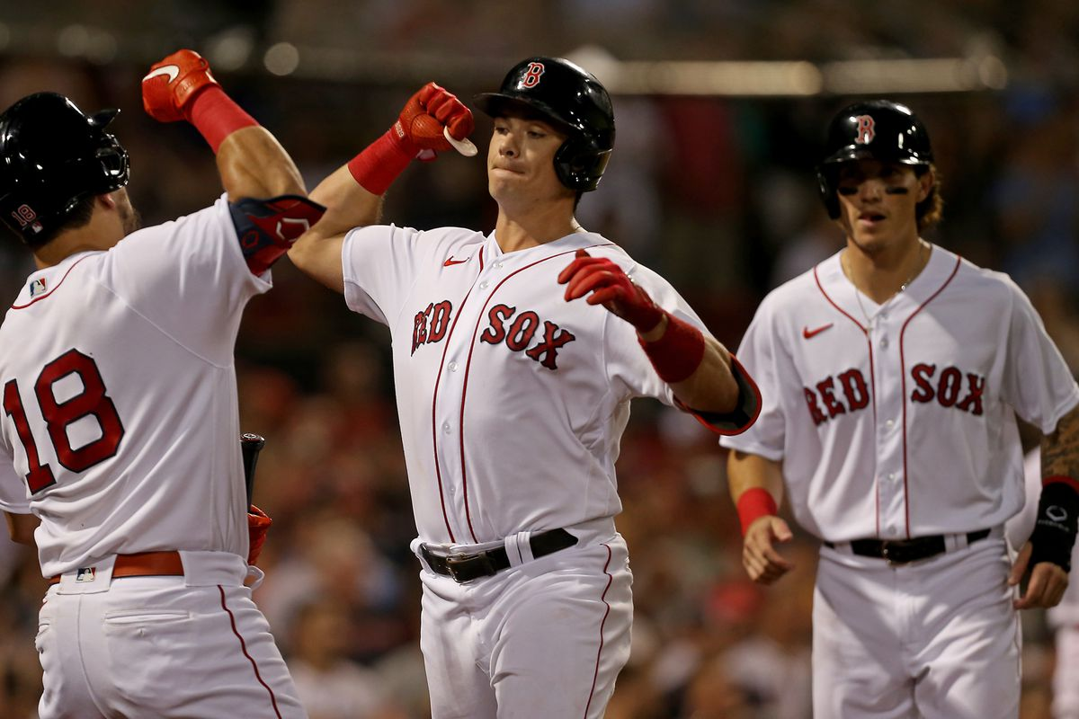 Bobby Dalbec #29 of the Boston Red Sox celebrates his three run homer with Kyle Schwarber #18 as Jarren Duran #40 looks on during the second inning of the MLB game against the Minnesota Twins at Fenway Park on August 26, 2021 in Boston, Massachusetts.