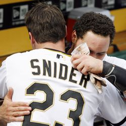 Pittsburgh Pirates right fielder Travis Snider (23) embraces catcher Russell Martin (right) after Snider drove in Martin with the game winning run during   the eleventh inning against the Cincinnati Reds.