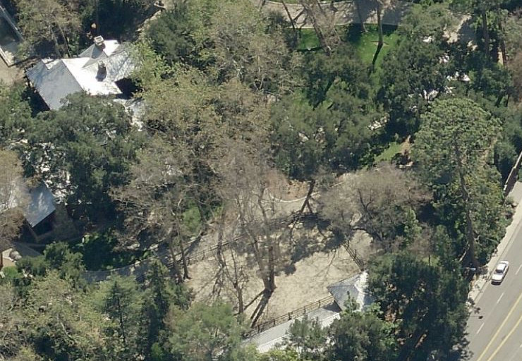 An aerial view of a house surrounded by trees. The house is white with multiple chimneys.