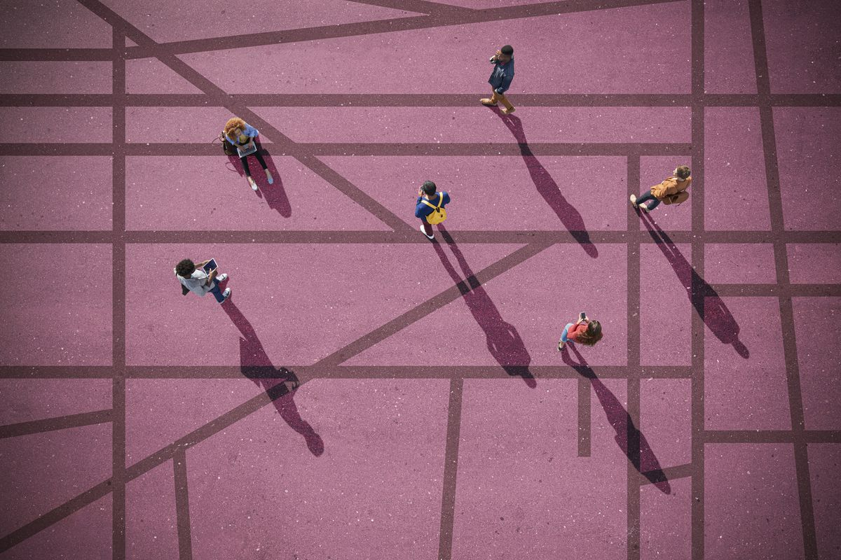 Young adults, photographed from above, on a tarmac surface painted with lines, at sunrise.