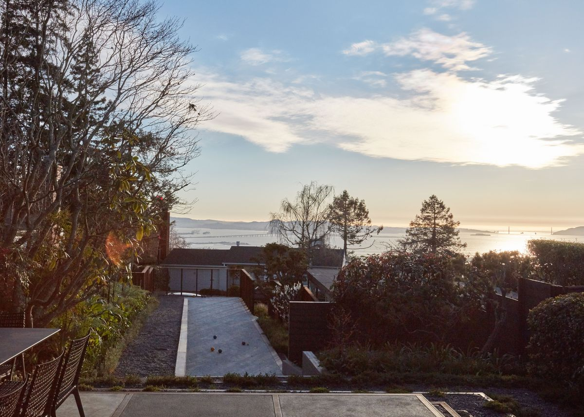 The exterior yard of a house. There is outdoor furniture, a table and chairs. There are trees. The view is overlooking a sunset and a body of water.