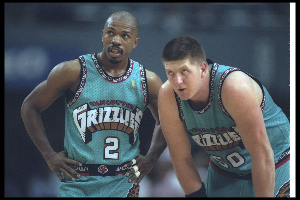 Greg Anthony and Bryant Reeves, playing for the Vancouver Grizzlies, huddle.