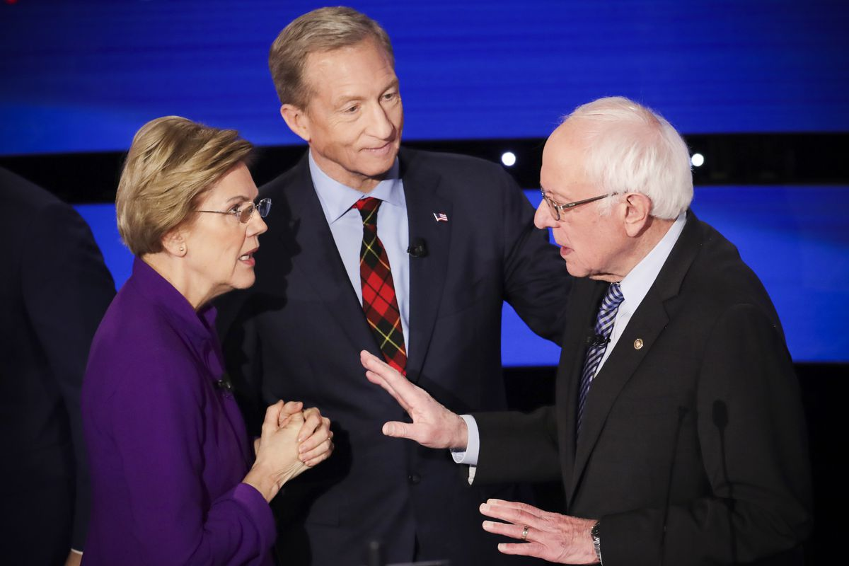 Senator Elizabeth Warren talks with Senator Bernie Sanders after a debate while candidate Tom Steyer looks on.