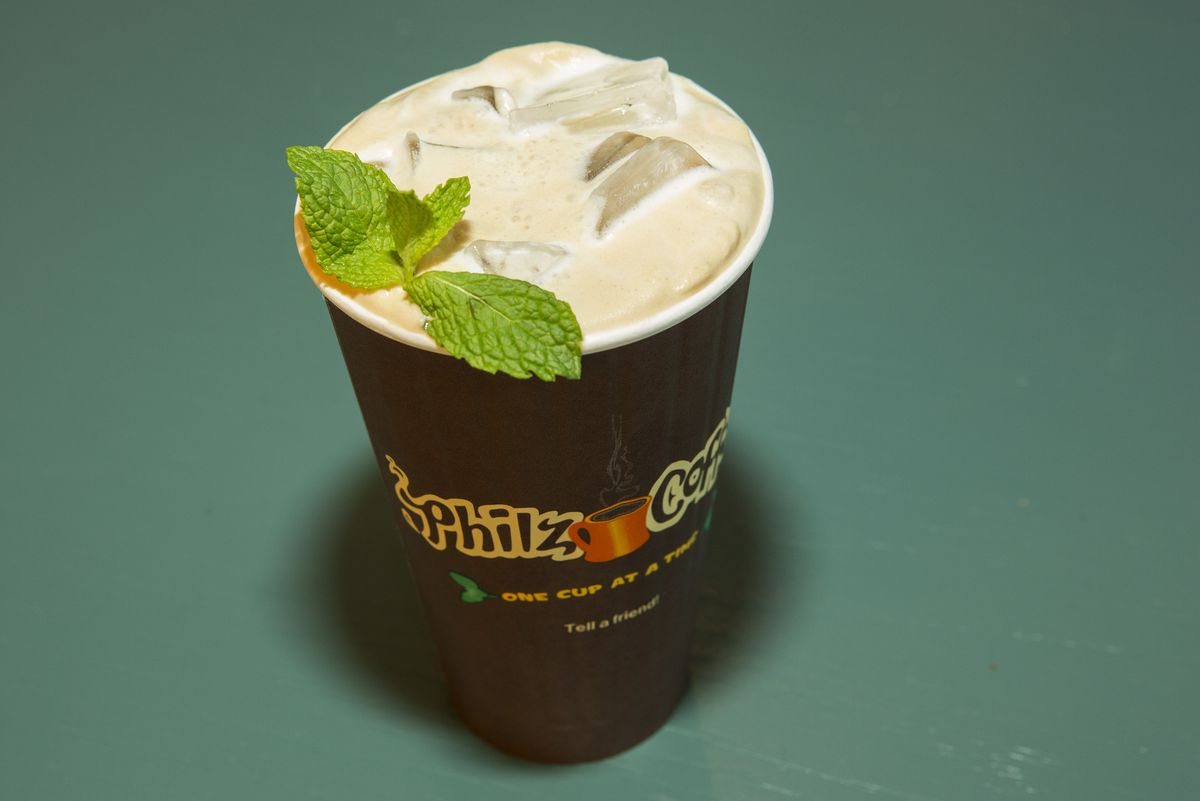 A brown paper cup of iced coffee with a sprig of green mint leaves.
