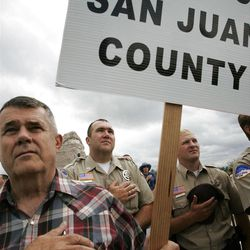 """Mike Halliday of Blanding, Utah, observes the singing of """"The Star-spangled Banner"""" along with San Juan County Sheriff's deputies John Laws and Lehi Lacy during the Take Back Utah rally at the Utah State Capitol in Salt Lake City, Saturday, Aug. 8, 2009."""