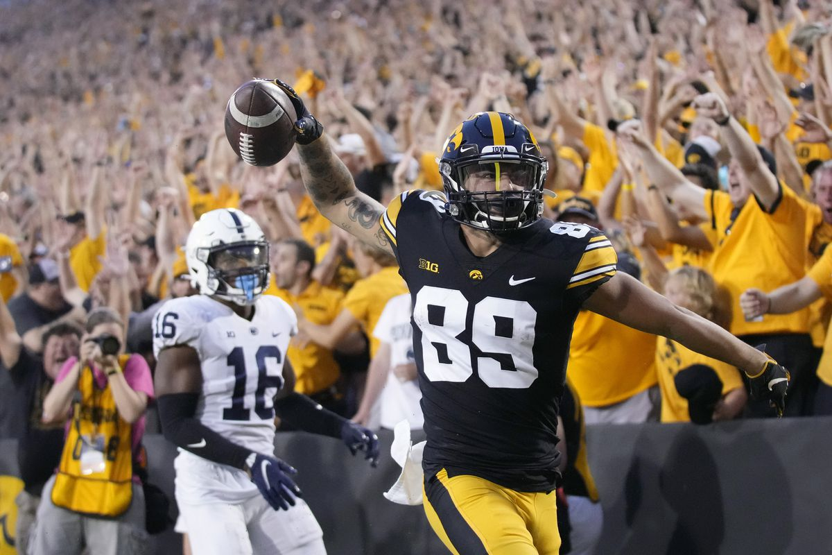 Iowa wide receiver Nico Ragaini (89) reacts after scoring a touchdown in front of Penn State safety Ji'Ayir Brown (16) during the Hawkeyes'  23-20 win Saturday.