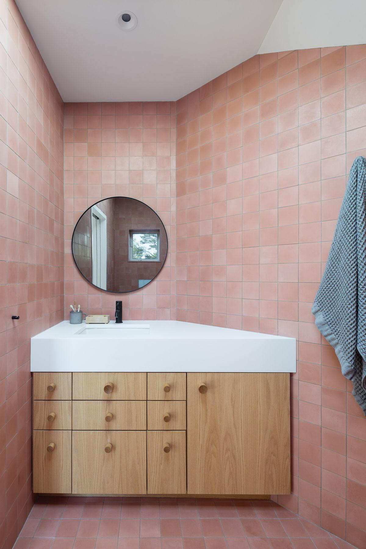 An irregularly shaped bathroom with pink tiles, wood cabinets, a jagged white sink, and round mirror.