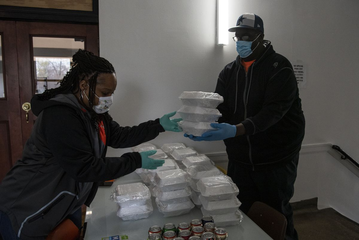 Tracy Crenshaw, left, hands a few boxes of food to Ernest Bryant, to be distributed to students and community members outside Leo High School, Friday, April 24, 2020.