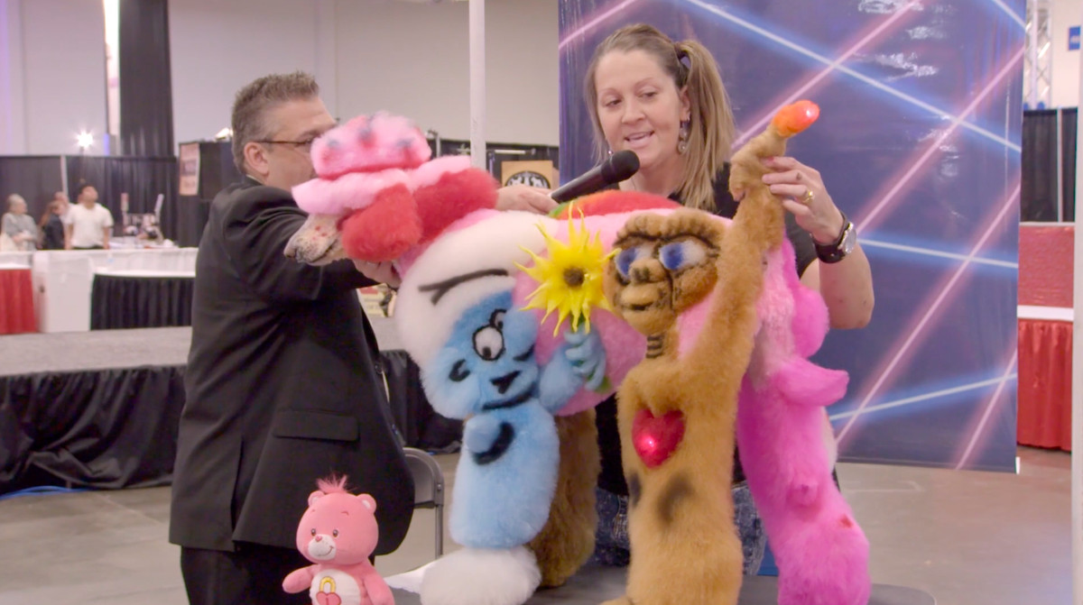 A groomer shows off her poodle, which has a smurf and E.T. dyed into its side, at a competition in Well Groomed