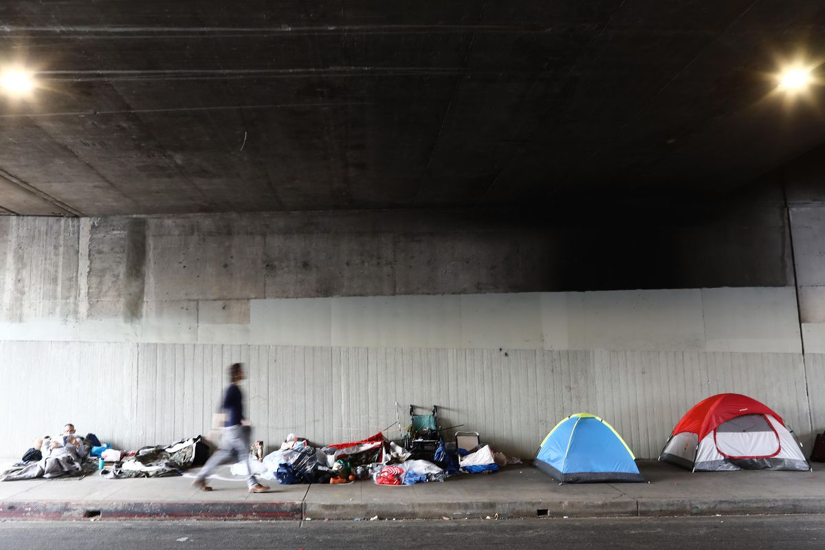 A man walks past a homeless encampment of colorful tents beneath the smooth concrete wall of a freeway overpass.
