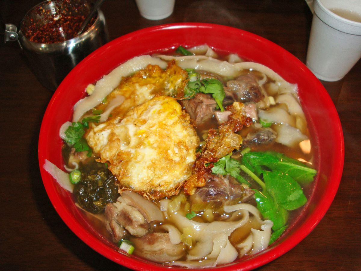 A bowl of thick noodles in soup with a fried egg on top.