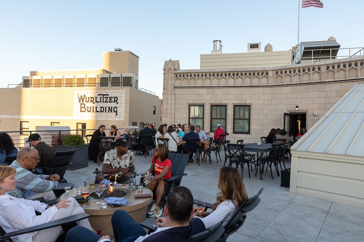 Crowd of people sitting around a fire pit on a rooftop with views of high-rise buildings