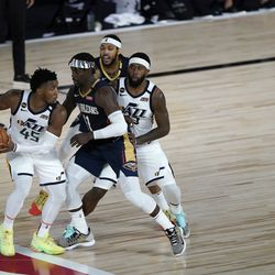 Utah Jazz's Donovan Mitchell (45) looks to pass around New Orleans Pelicans' Jrue Holiday (11) during the second half of an NBA basketball game Thursday, July 30, 2020, in Lake Buena Vista, Fla. (AP Photo/Ashley Landis, Pool)