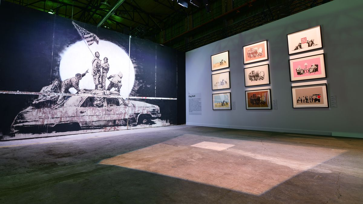 """""""The Art of Banksy"""" exhibit features """"Flag Wall"""" among 80 works created by the mysterious artist."""