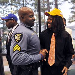 Athens-Clarke Police Sgt. Kenny Brown, left, shakes hands with Clarke Central's Queshaun Watson during a national signing day ceremony at Clarke Central High School on Wednesday, Feb. 1, 2012 in Athens, Ga. Watson signed a letter of intent to attend the University of Tennessee.