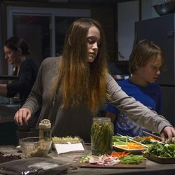 Vegan chef Molly Aubuchon prepares broth as her children, Emma, 13, center, and Sam, 11, right, choose their vegan noodle bowl ingredients Monday, Feb. 8, 2016, in her Kent, Ohio, home.