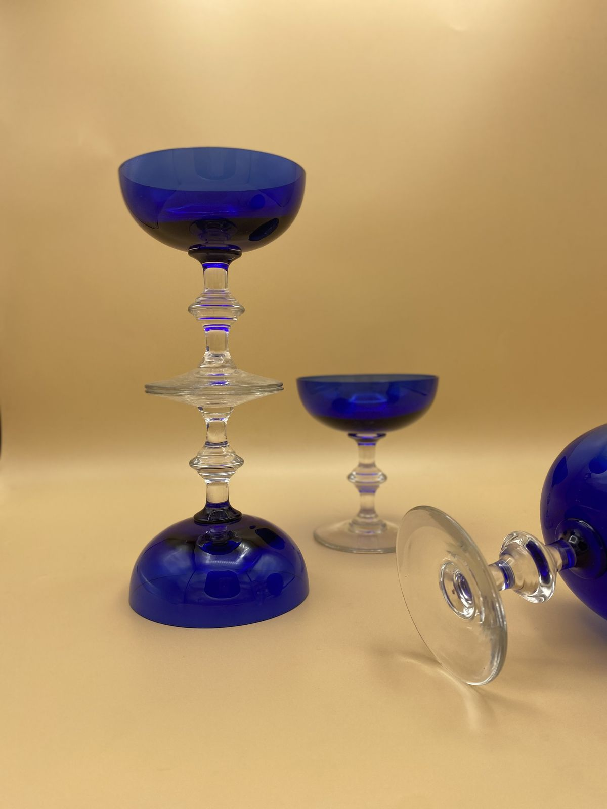 Four coupe glasses with blue bowls and clear stems