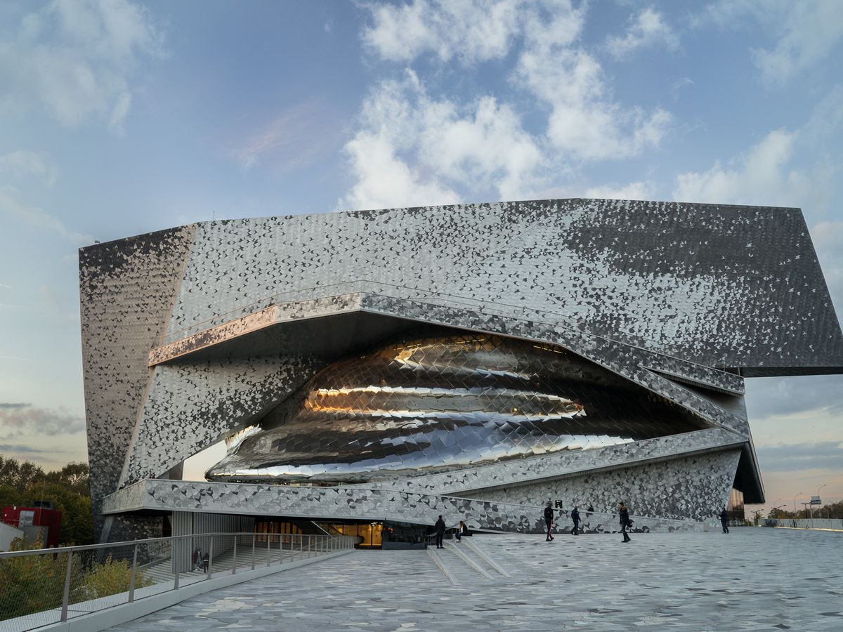The exterior of the Philharmonie de Paris. The facade is metallic and the building has a geometric structural shape.