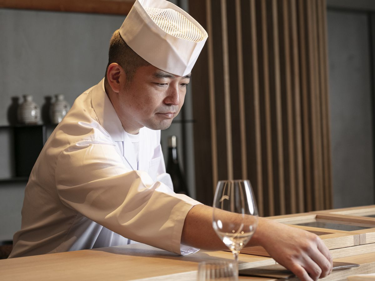 A man in a white chef's outfit and hat stands at a sushi counter, setting a table for service