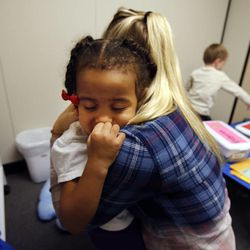 Edynn gets a hug from Jayme Duringer before taking a break as she participates in therapy work sessions during the Autism Bridges program at Kids on the Move in Orem, Tuesday, Oct. 15, 2013.