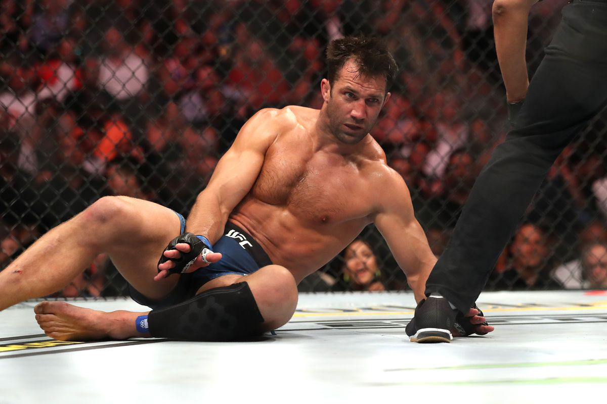 Luke Rockhold's tries to get back up to his feet after being knocked out by Jan Blachowicz in 2019.
