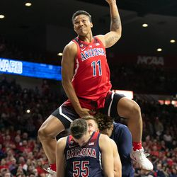 Ira Lee (11) leaps over three fellow teammates during the 2018 Red-Blue dunk contest in McKale Center on October 14 in Tucson, Ariz.