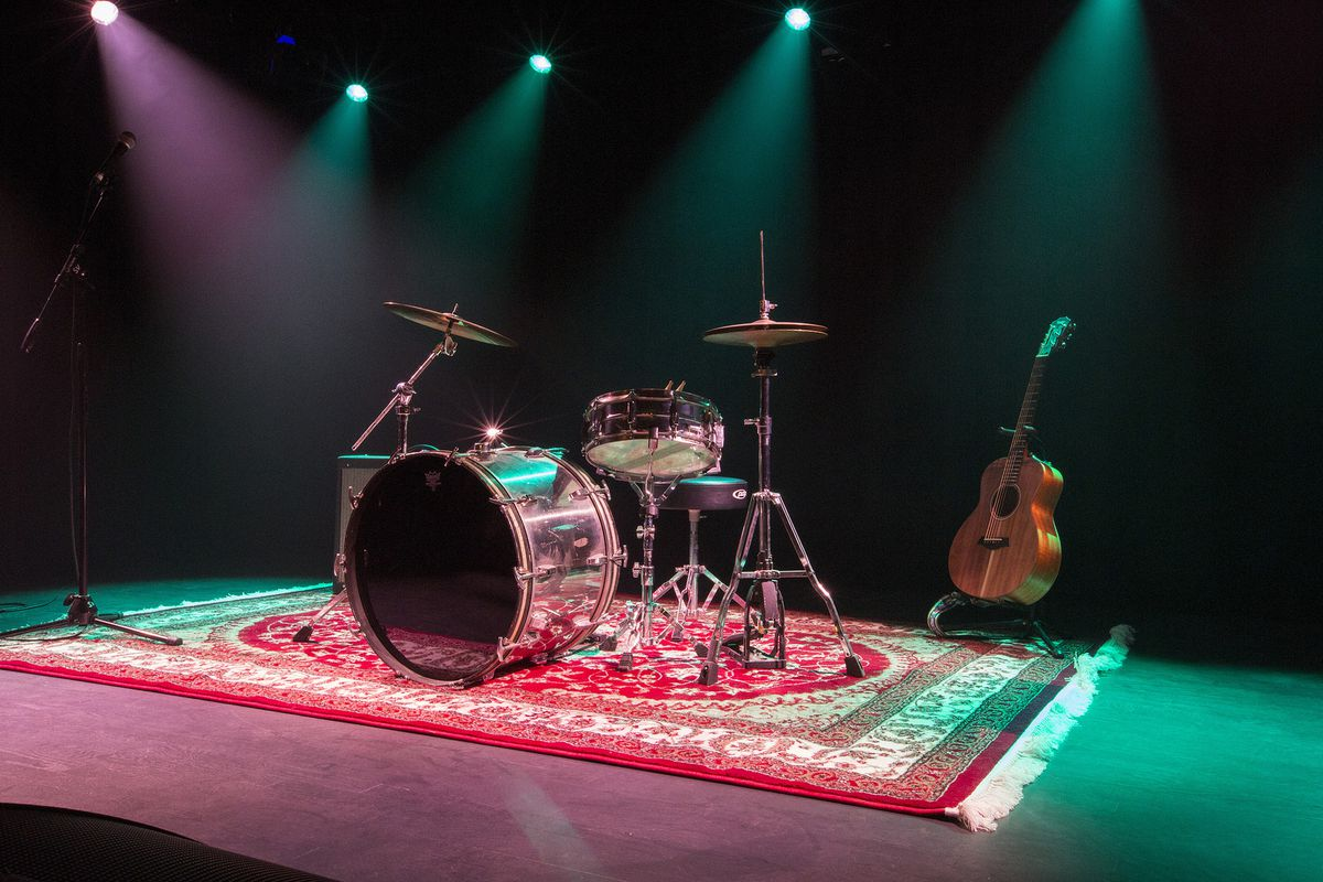 An empty stage with a drum kit.