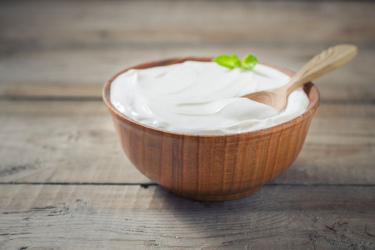 A bowl of yogurt on a wooden table.