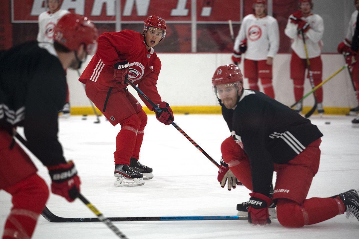 A pass to Sebastian Aho is blocked off by Dougie Hamilton during day three of training camp at Wake Competition Center, Jan. 6, 2021.
