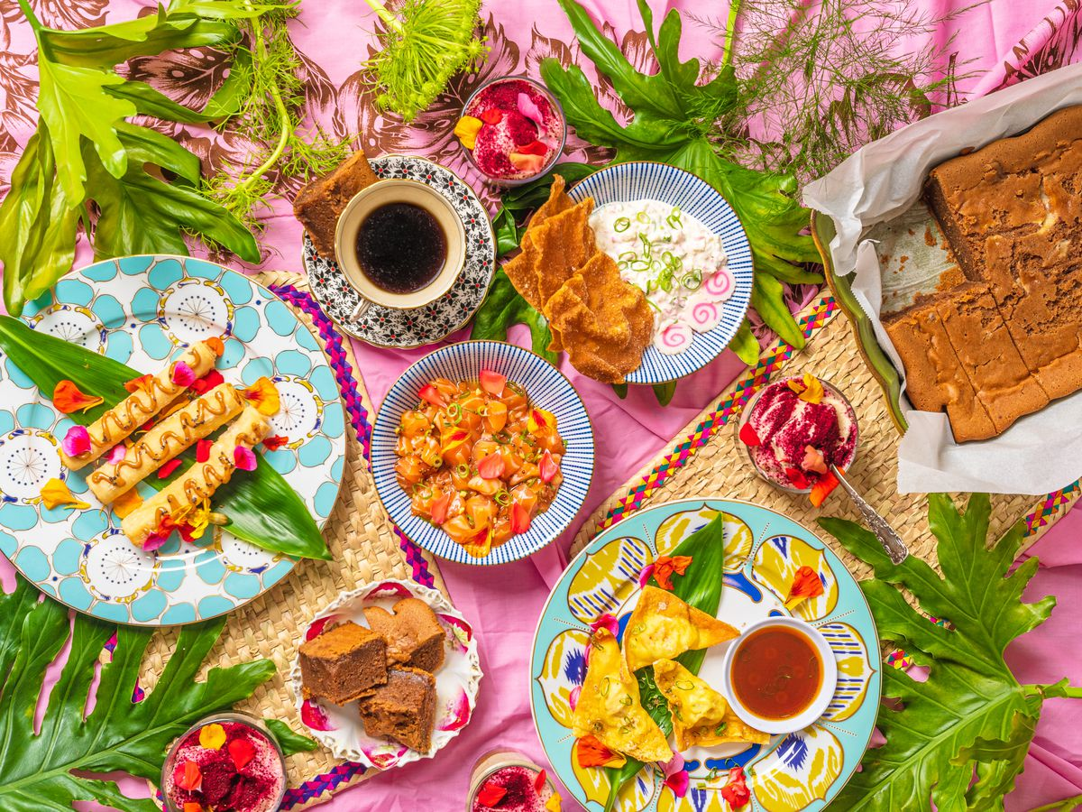 A pink background with an array of fresh greens and Hawaiian dishes from Kiki Arinata.