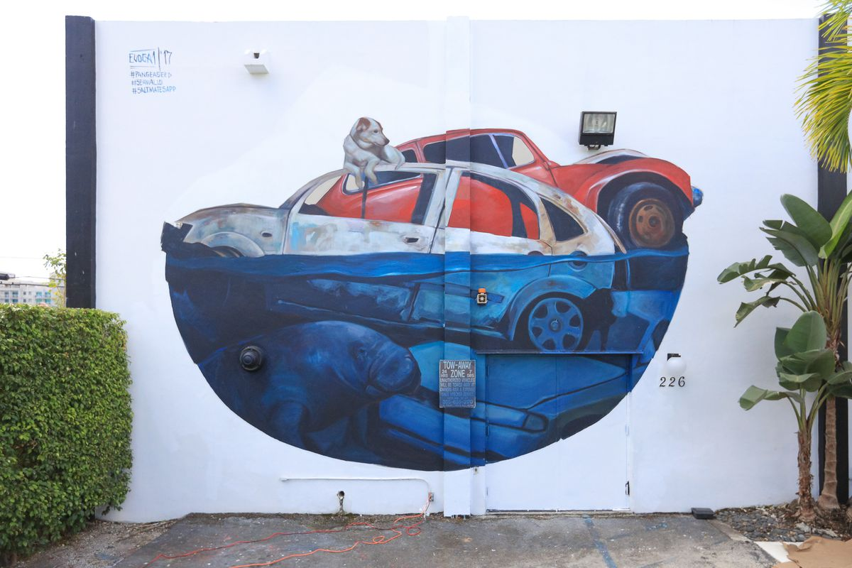 a mural of a dog on top of a drowning car with a manatee underneath
