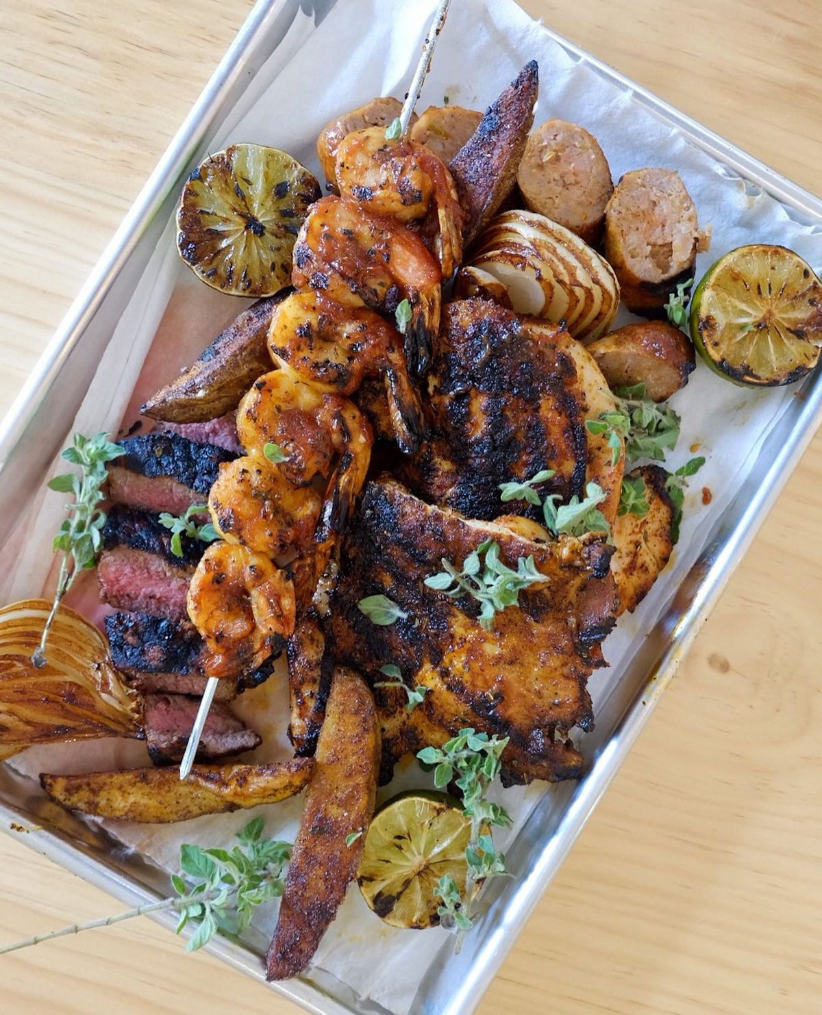 A half grilled and brined chicken and steak with BBQ shrimp skewers and potato wedges and grilled half onions on a silver serving tray