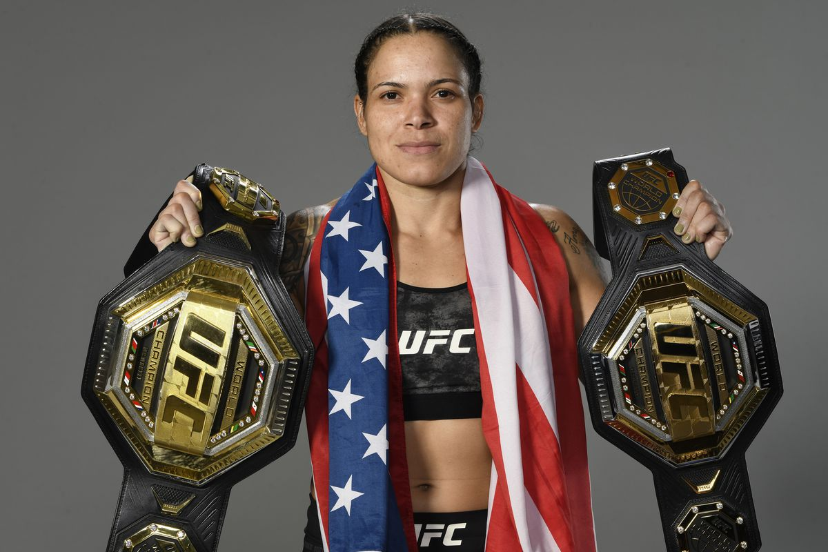 Amanda Nunes with her two titles after UFC 259.