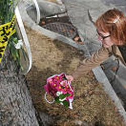 Cece Russell-Jayne, South Ogden, leaves flowers at Trolley Square Tuesday morning.