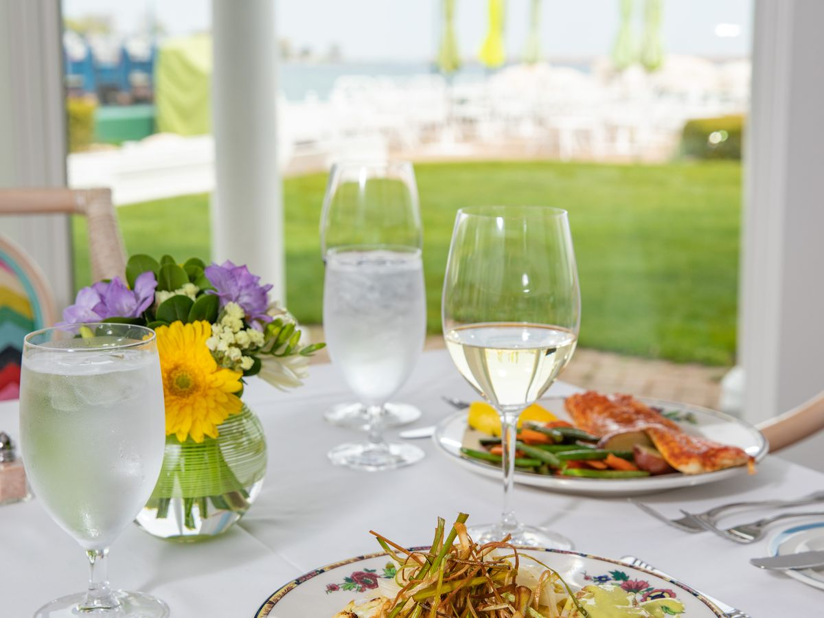 Two plates on a white-tablecloth table with glasses of water. There's a slight view of grass and the outdoors in the background