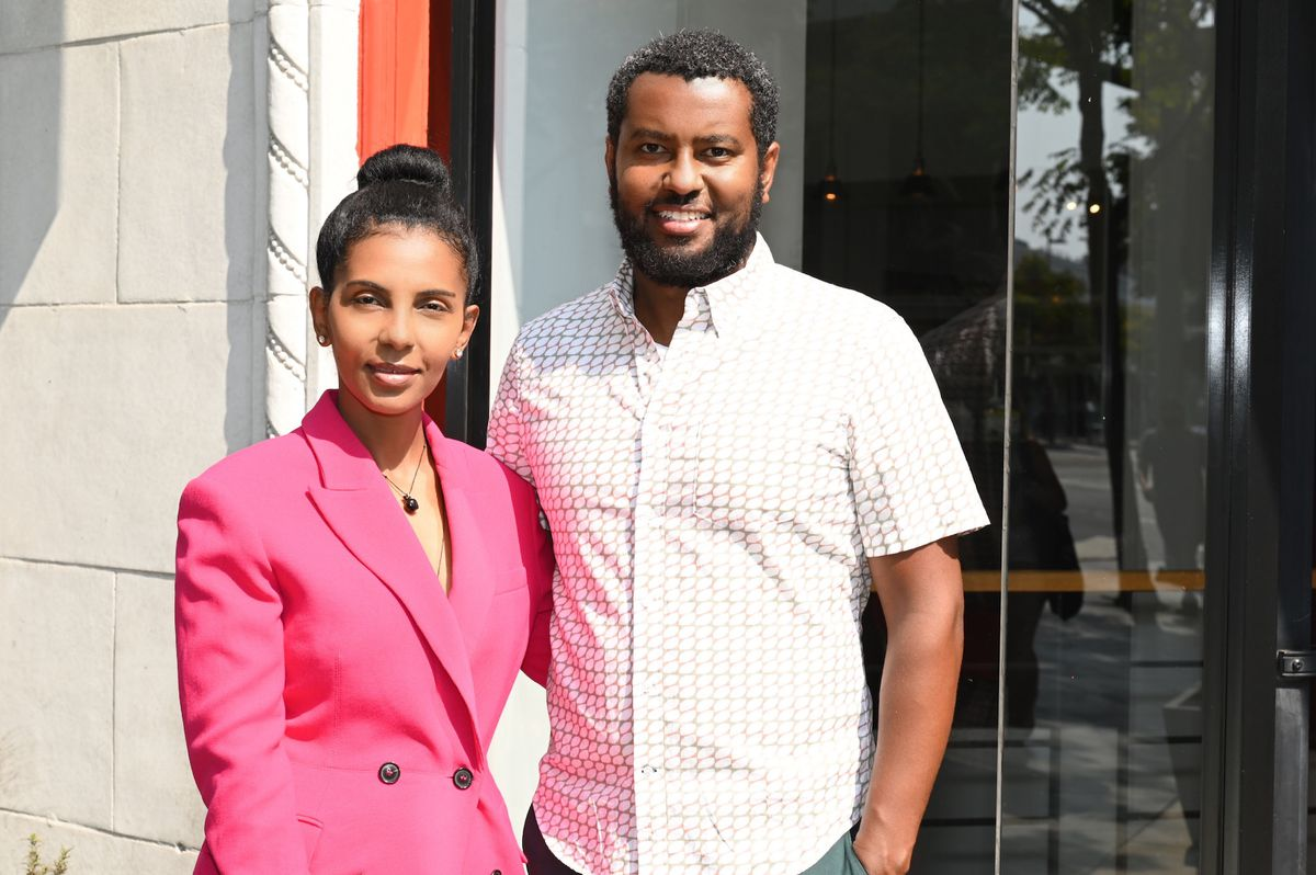 A couple of business owners, including one in a pink suit, stand in front of their Ethiopian restaurant.