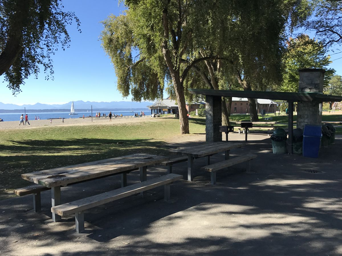 A picnic shelter and two picnic tables along a lawn, with a beach in the distance.