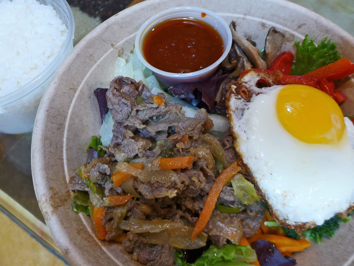 A recyclable brown bowl with a sunny side up egg, heap of shredded beef, and dark red sauce in a little plastic up placed on top of the dish.