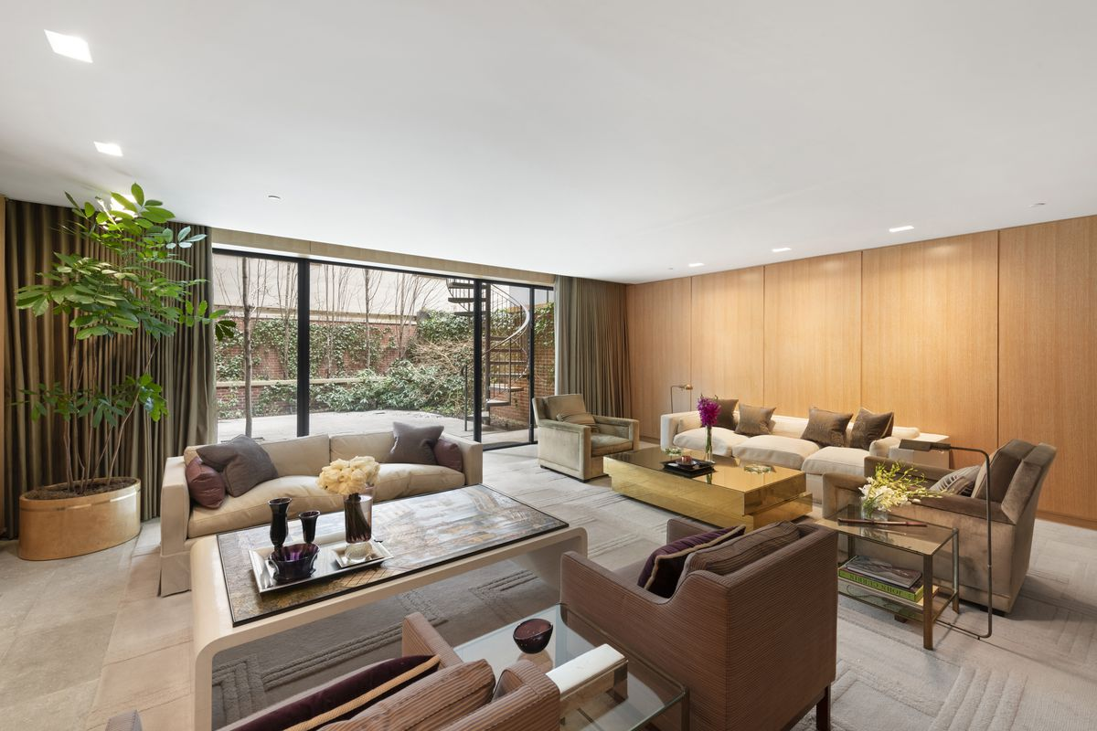 A living room with two beige couches, several chairs, a large planter, and a glass door that leads to a courtyard.
