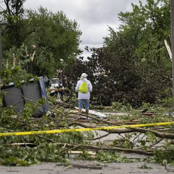 A resident surveys the damage on Janes Avenue near Evergreen Lane in Woodridge after a tornado ripped through the western suburbs overnight, Monday morning, June 21, 2021.