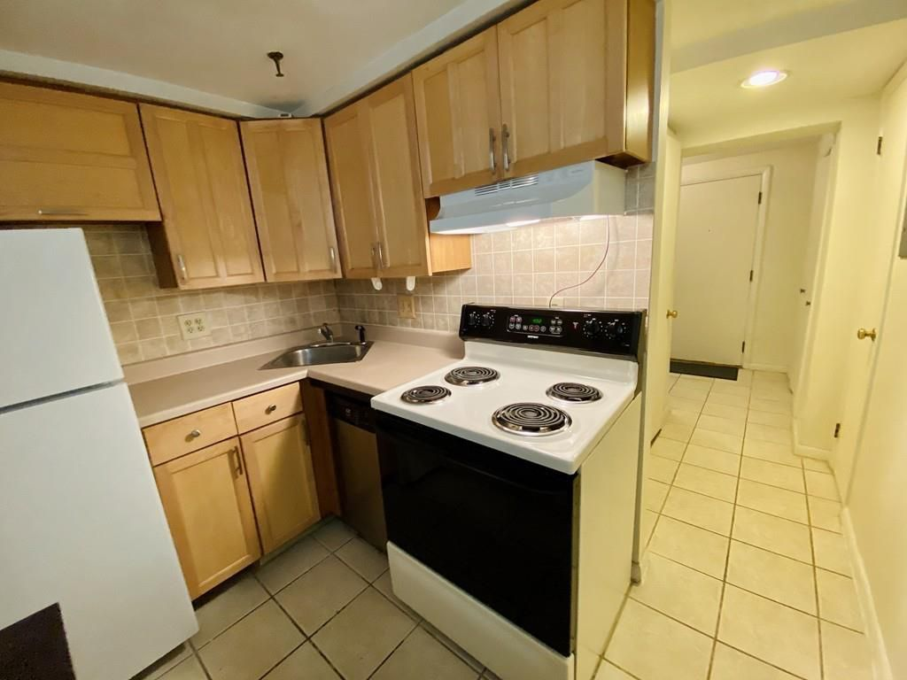 A small, older kitchen with cabinetry and an electric stove.